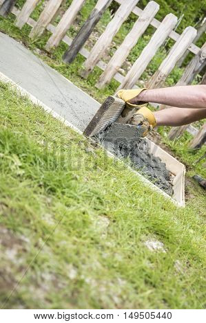Close up of the gloved hands of a man laying a concrete slab in the garden in a wooden frame on the grass in a DIY concept.