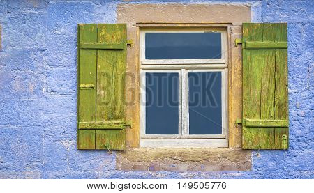 German window with shutters - Aged wooden window and green shutters from an old german house with blueish painted wall stone