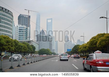 SHANGHAI - NOV 5, 2015: Cars on road, Shanghai Tower and Shanghai World Financial Center, Shanghai has population of 24,6 millions people