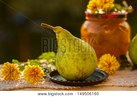 pear jam in jar and fresh pears on nature. Fresh sweet fruit delicacy. Agriculture concept. Food photo. Wooden background. Designers capture. Table with Welded yellow pears with flowers