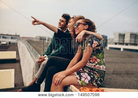 Man and women sitting on roof terrace and looking away smiling. Happy young friends relaxing on rooftop with woman pointing at something interesting.