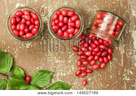 Jars of dogwood berries compote on wooden table with fresh green leaves