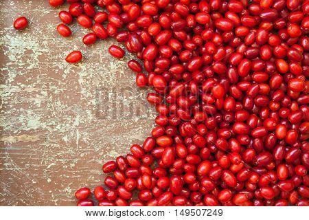 Freshly picked cornelian cherries on wooden board