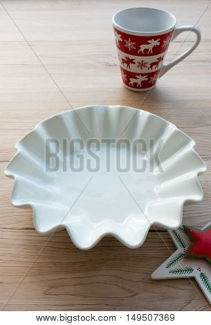 Empty white porcelain bowl and Christmas mug on light brown wooden background with Star as decoration.