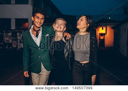 Shot of young friends walking down street in the evening and smiling. Multiethnic group of people enjoying a walk outdoors in the city.