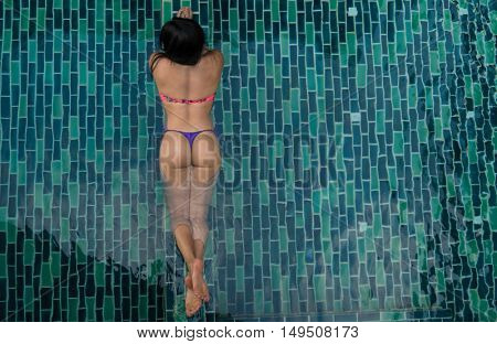 Top back view of sexy brunette woman in bikini relaxing in the pool