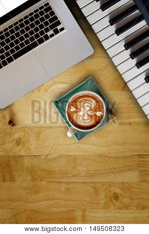 Green Cup of coffee electric piano keys and laptop on wooden table.