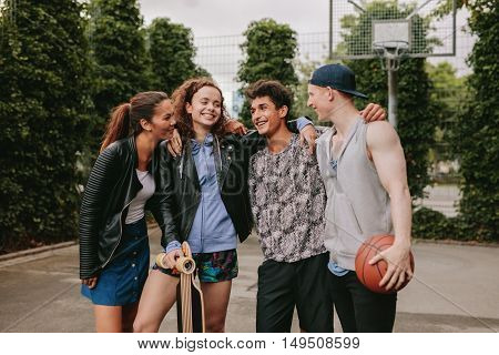 Four Young Friends Standing Together Outdoors
