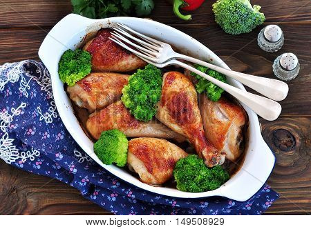 Baked chicken drumstick with organic broccoli on a wooden background.