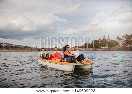 Shot of four young people on pedal boat in lake. Women sitting on front with men at back pedaling the boat.