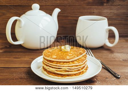 Stack of tasty pancakes with butter and honey for breakfast