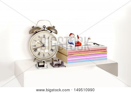 Alarm clock and books on nightstand on a bright lit room