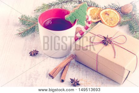 Homemade butter nuts christmas tree shaped cookie with icing pine orange slicescinnamon anise and walnuts over white wood background. A cup of berry tea and a gift box wrapped in kraft paper. Christmas decoration.