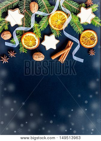 Christmas decoration over dark wood background. Top view of homemade butter nuts star shaped cookies with icing pine orange slicescinnamon anise walnuts and white ribbon.