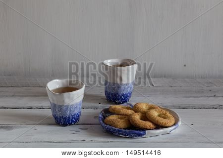 tea in ceramic cups blue and white hand-made ceramic tableware cookies on a ceramic plate a pair of clay cup on a white background.