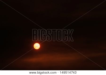 Summer sunset and orange sun over dramatic red clouds