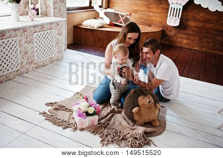 Young Happy Family With Son Lying On Plaid Blanket And Hedgehog Toy