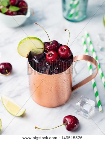 Cold cherry Moscow Mules cocktail with ginger beer, vodka, lime Marble background Copy space