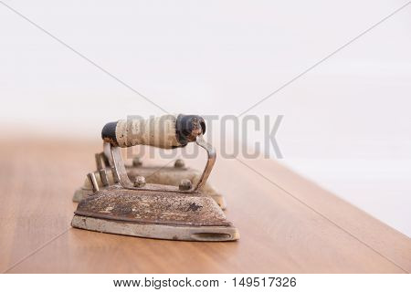 Small antique iron over naturally blurred background