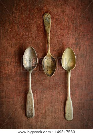 three vintage teaspoons  on a brown wooden background