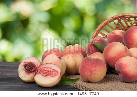 peaches on a wooden table with a blurred background.