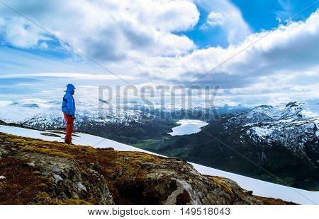 Tourist stands on a hilltop and look at the lake in the valley. Blue sky with clouds. Snowy mountains. Norway.