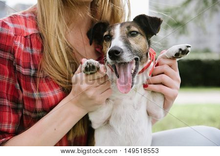 Funny smiling dog with her master. Girl holds the dog's paws to pose.