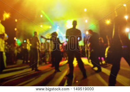 young people dancing and having fun at night disco blurred backgroud