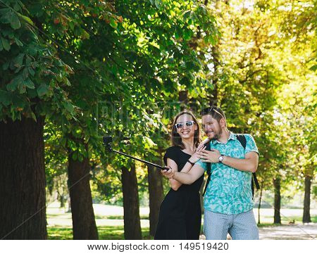 Friends Or Couple Of Lovers Making Selfie Photo On Gopro Camera In Park Of Europe.