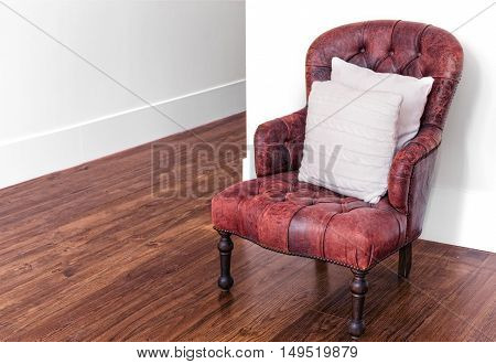 Classic luxury red leather armchair on wood floor