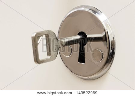 The key is inserted into the keyhole on a white background closeup