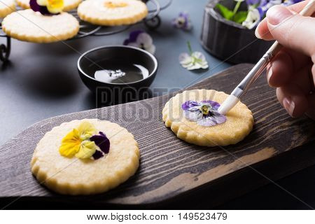 Process of making shortbread cookies with edible flowers on old wooden background. Holiday food