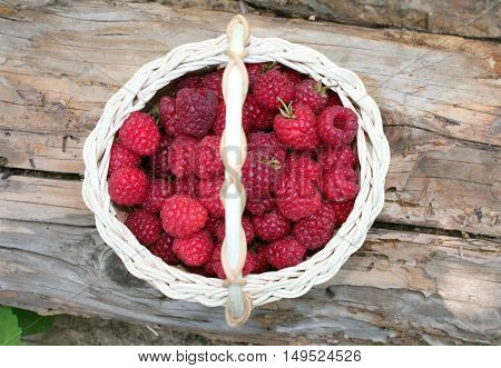 Raspberries in basket on wooden background top view