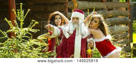Santa Claus winks and holds christmas ornament with sexy girls around. Outdoor celebration of new year with attractive ladies and man in a costume