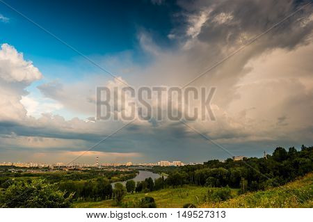 Beautiful natural landscape at sunset with green grass, flowers and cloudy sky. City building in distance. Image of recreation in countryside. Great outdoors picture.