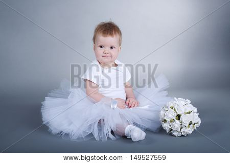 photo of cute little girl with bouquet on grey