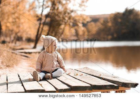 Stylish baby girl 1 year old wearing knitted autumn clothes sitting in park. Looking away. Childhood.