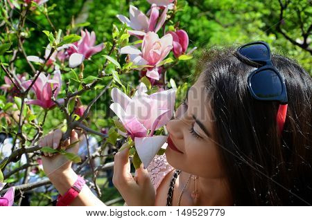 spring in the garden of a charming girl and beautiful large fragrant flowers of magnolia