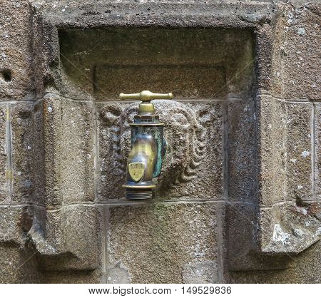 Valve to the water built-in decorative manner in the wall in the mouth of a lion. Tourist attraction of Mont Saint-Michel in France