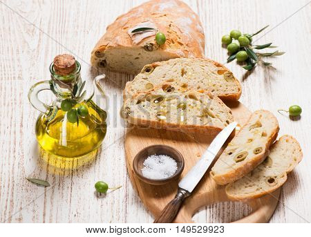 Tasty white bread with olives and olive oil on a rustic wooden background.