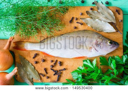 Raw perch on rustic cutting board with fresh herbs, vegetables and spices on green wooden table. Top view.