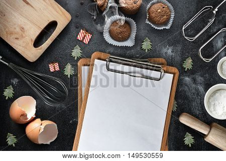 A blank clipboard with kitchen utensils and christmas toys on black background copy-space.