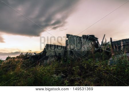The remains of the destroyed buildings in the background of dark sky