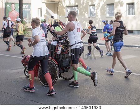 BERLIN GERMANY - SEPTEMBER 25 2016: Marathon runners run at Berlin Marathon 2016 in the city center of Berlin. One pushes a man in a wheelchair.