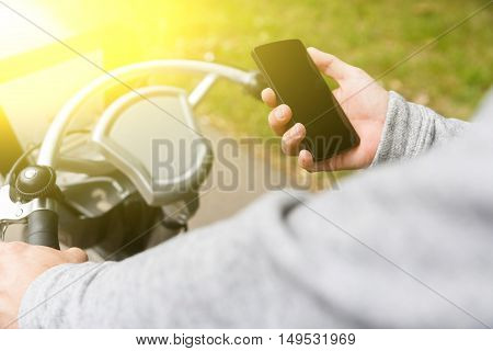 Man rides bicycle and holding mobile phone on summer day. Image with lens flare effect
