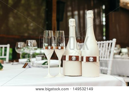 Wedding event. Chiavari chairs on the covered wooden deck. On a table decorated with a bottle of champagne and glasses.