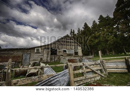 Old dilapidated shearing shed against a dynamic cloudy blue sky background