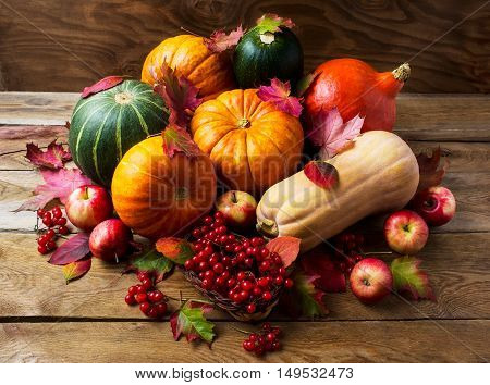 Abundant harvest concept with pumpkins apples and berries. Thanksgiving background with seasonal vegetables and fruits. Fall background.