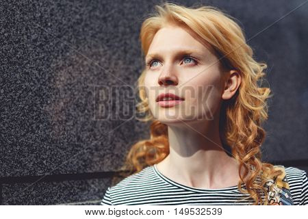 Ginger girl close-up near gray marble wall, tinted photo