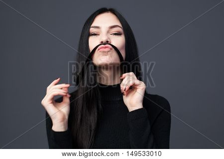 Young brunette woman is playing with long hair and making mustache of it gray background